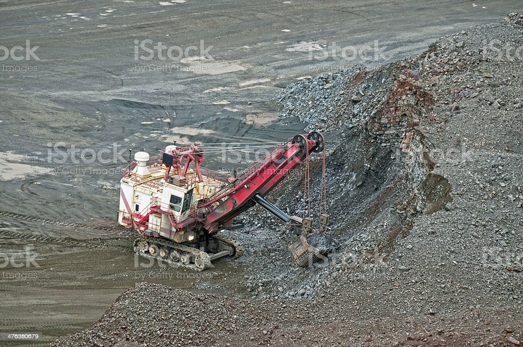 Crane with bucket digging out iron ore from blast site royalty-free stock photo