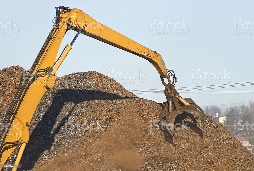 Crane with grab attachment sorting shredded scrap metal royalty-free stock photo