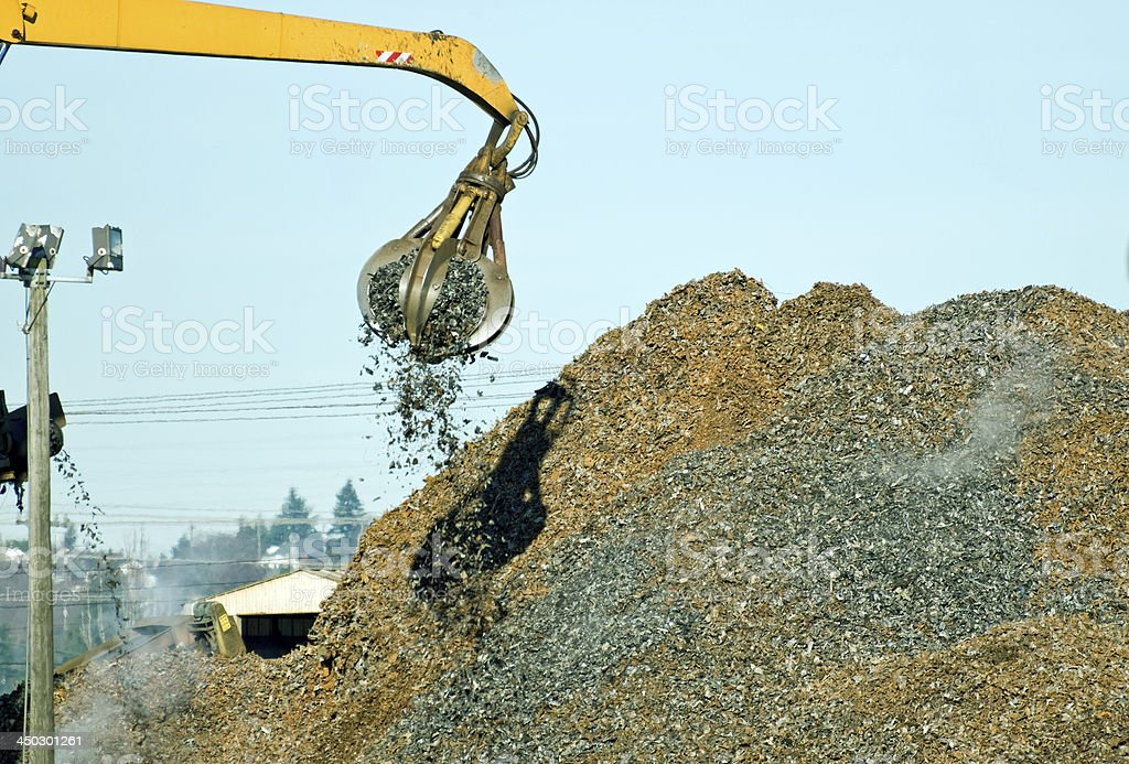 Crane with grapple attachment moving shredded metal onto pile stock photo