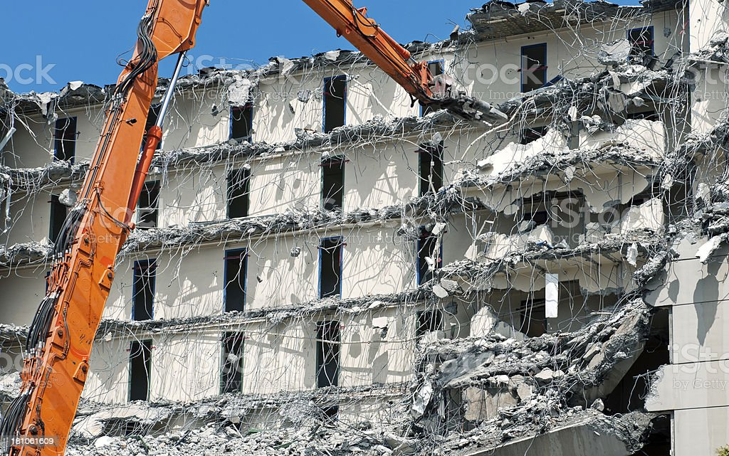 Crane with shearing tool cutting rebar in demolished building stock photo
