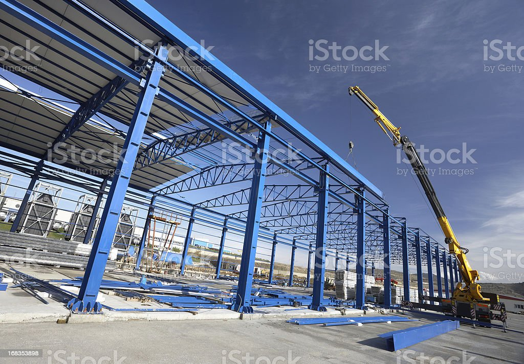 A crane working on a factory building stock photo