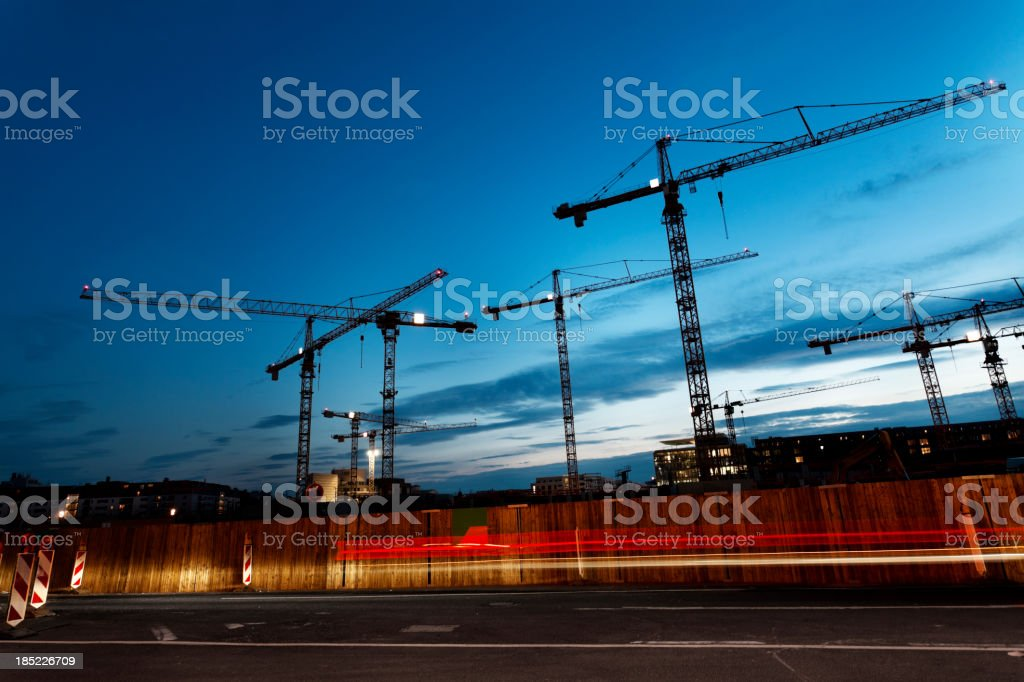 Cranes against blue sky at dusk stock photo