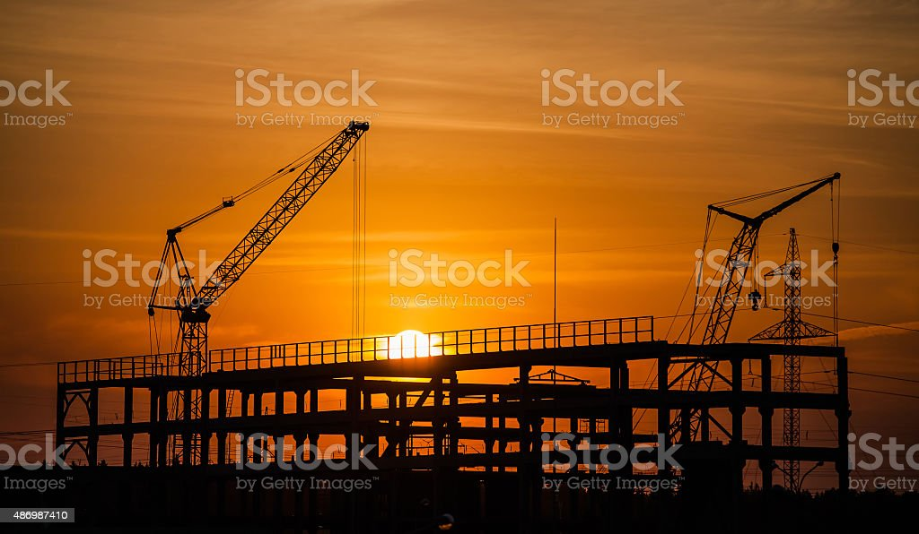 cranes and buildings under construction against the setting sun stock photo