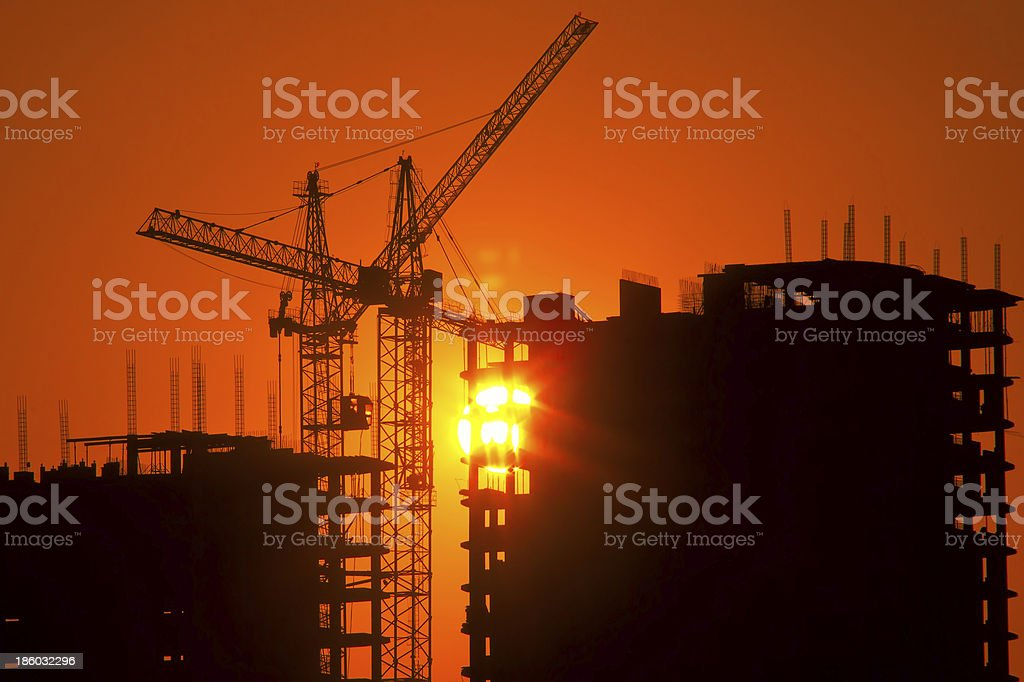 cranes and buildings under construction at sunset royalty-free stock photo