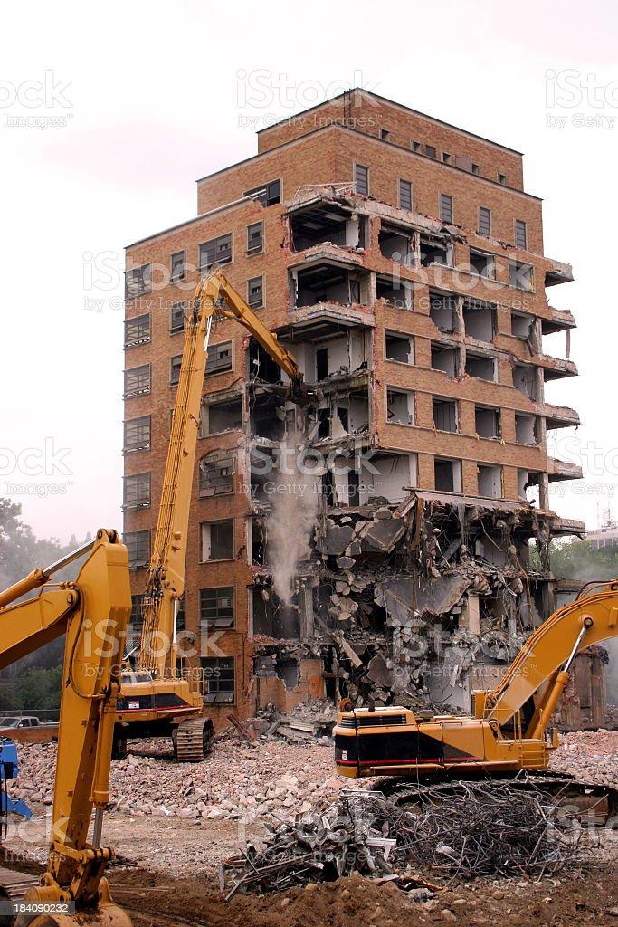 Cranes demolishing a brick building royalty-free stock photo