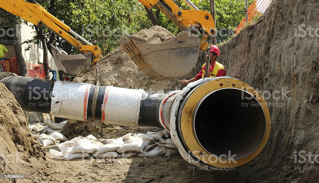 Cranes holding pipe at construction site stock photo