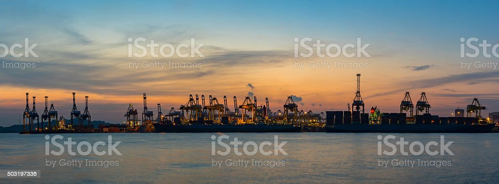 Cranes loading containers at a ship yard. stock photo