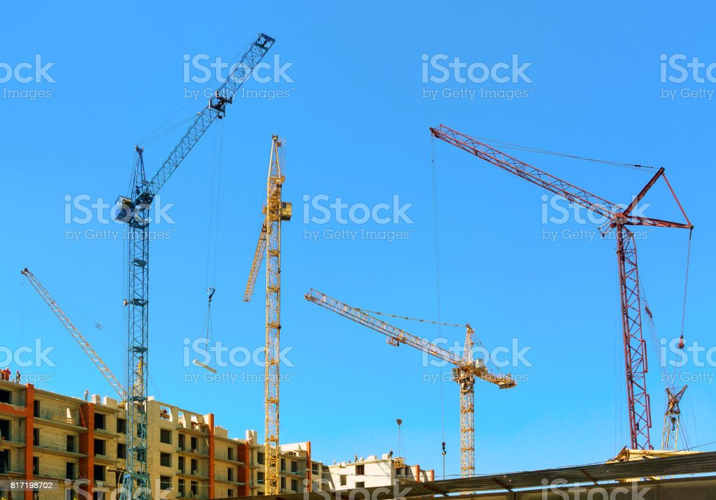 cranes under a blue sky stock photo