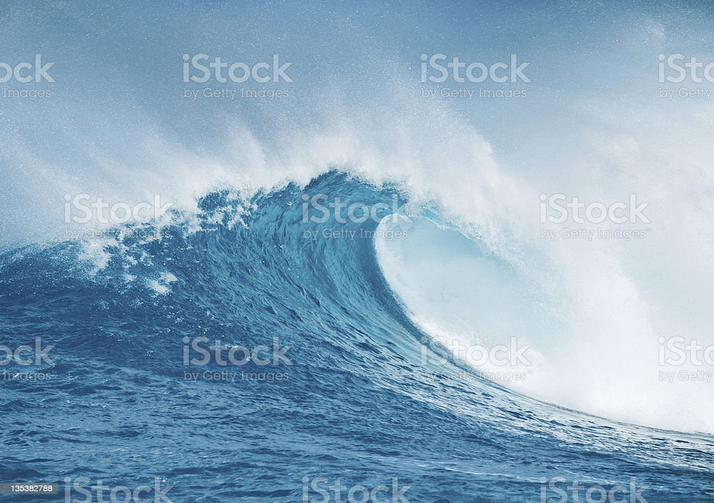 Crashing ocean wave against blue sky in Hawaii stock photo