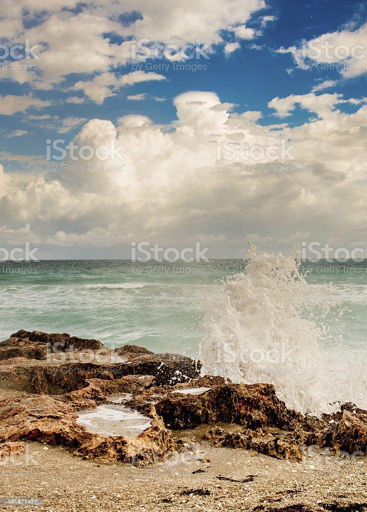 Crashing Wave under White Clouds stock photo