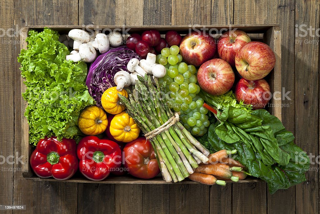 Crate full of fruits and vegetables over rustic table stock photo