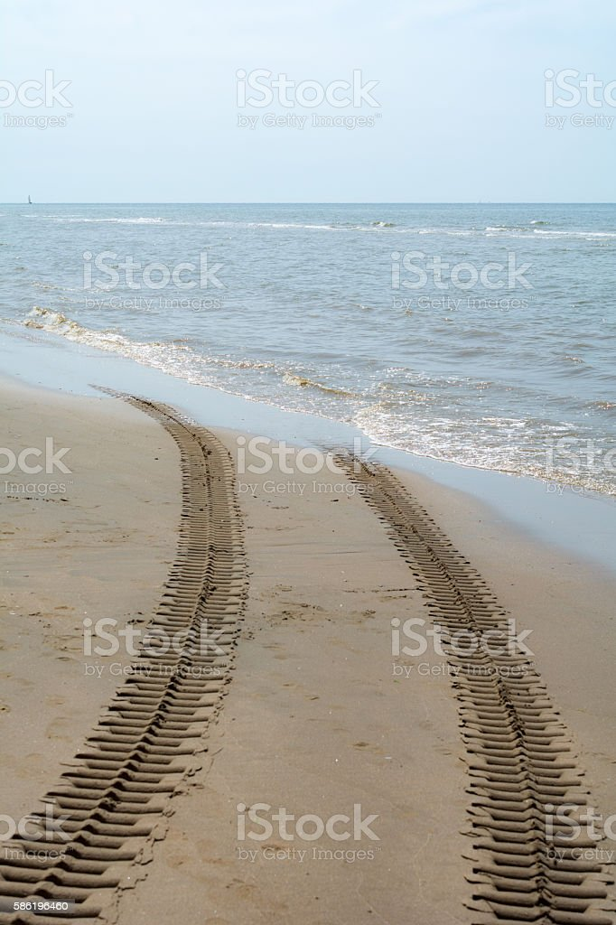 Crawler track disappearing into the sea stock photo