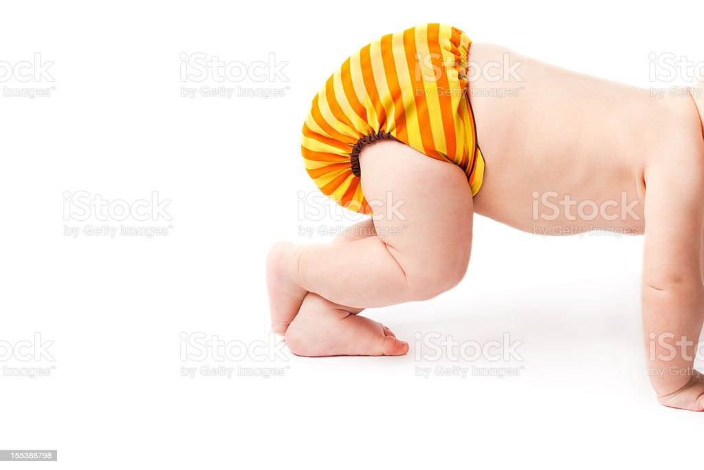Crawling baby lifting cloth diaper high up stock photo