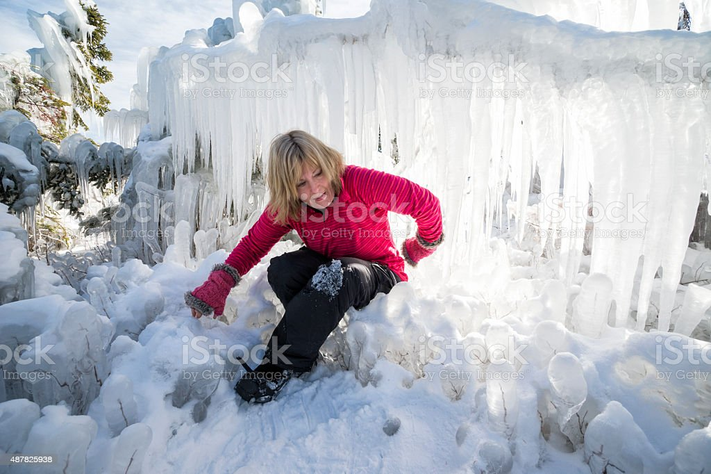 Crawling out of a tight space among icicles stock photo