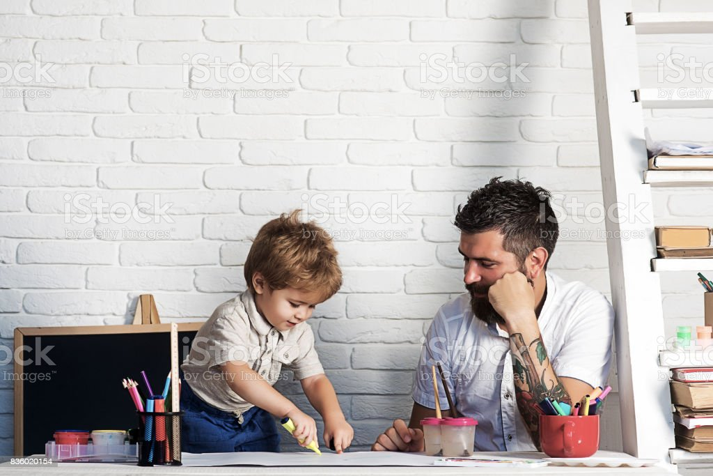 Crayons drawing family, father looks how son draws. Development of motor skills and thinking in children garden, teacher and pedagogy, art therapy. Small artist paints with felt-tip pens and fingers stock photo