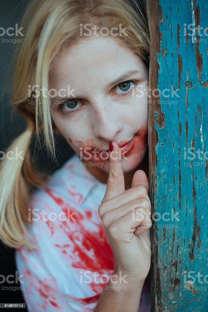 Crazy blonde woman covered with blood making silence gesture stock photo