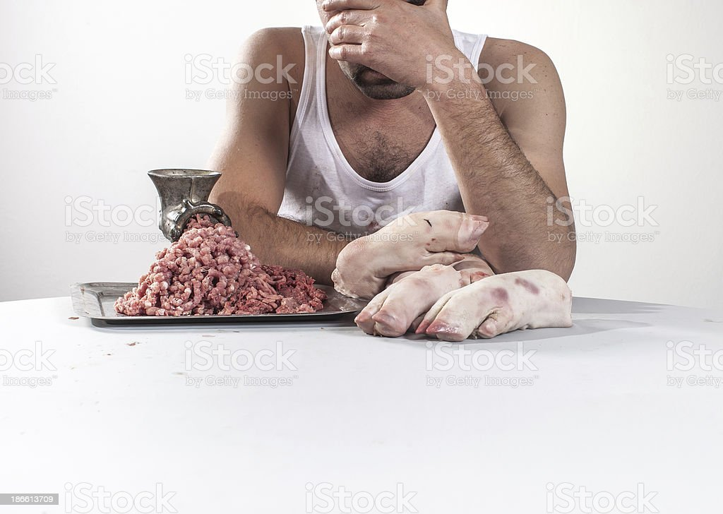 Crazy butcher with pork meat behind the table royalty-free stock photo