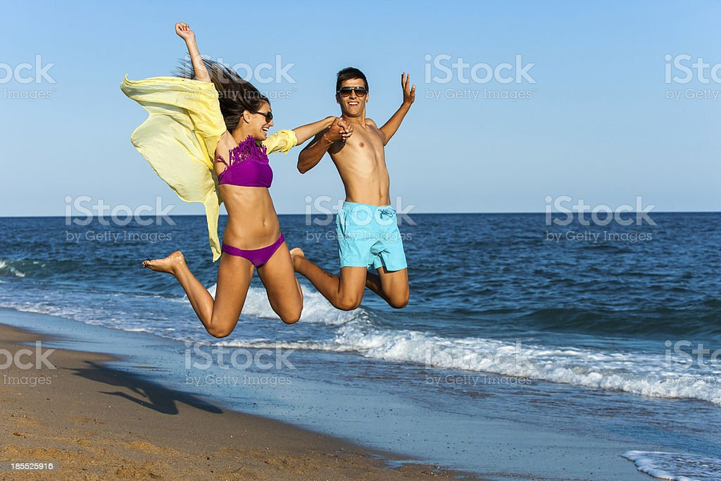 Crazy couple de sauter sur la plage. photo libre de droits
