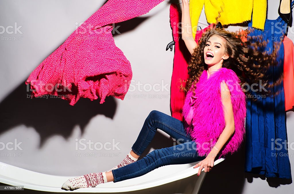 Crazy emotional young woman with clothes on bathtub stock photo