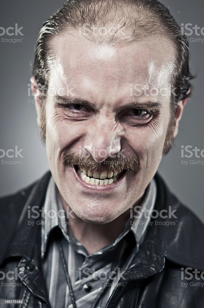 Close up of a sketchy looking man with an evil grin.