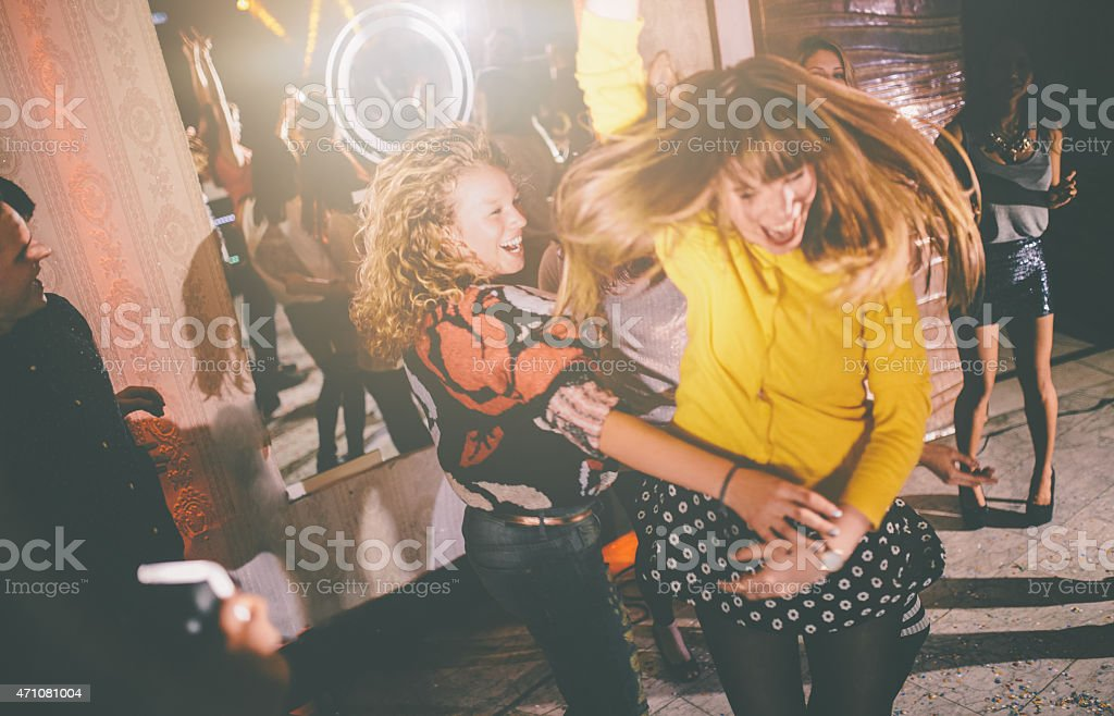 Crazy friends dancing wildly at a party in a club stock photo