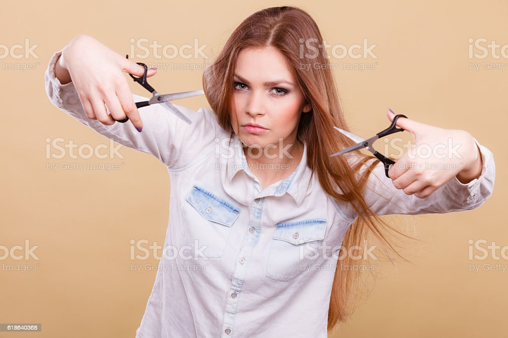 Crazy girl with scissors. Hairdresser in action. stock photo