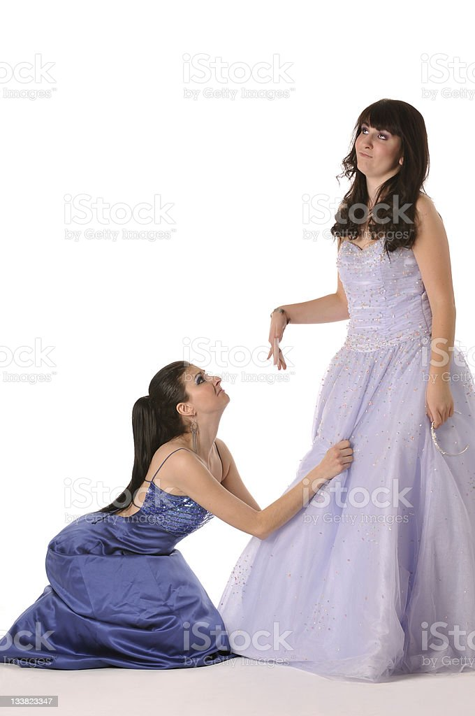 Crazy girls in graduation gowns, one begging, the other ignoring stock photo