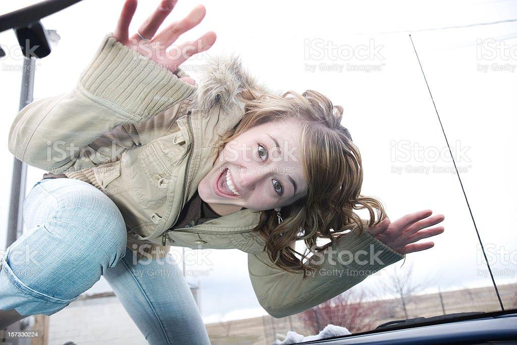 Crazy Happy Teenage Girl on Car Glass Windshield royalty-free stock photo