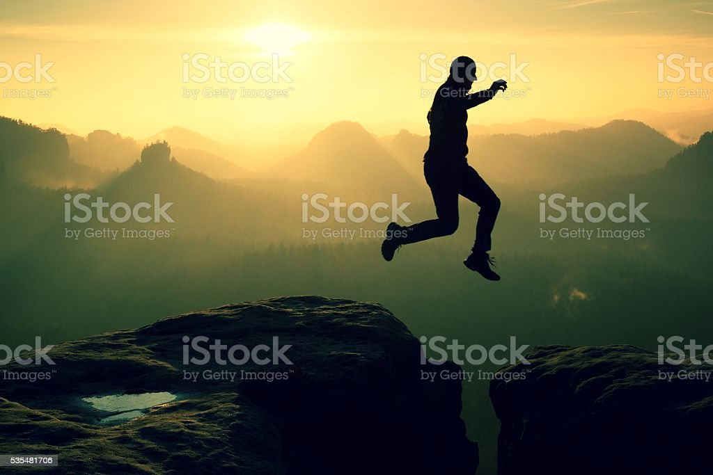 Crazy hiker jump between cliffs. Amazing mountains, heavy mist stock photo