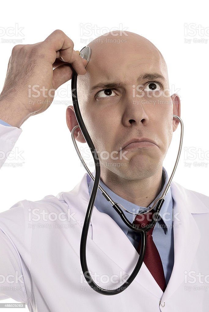 Crazy male doctor holding a stethosope to his forehead stock photo