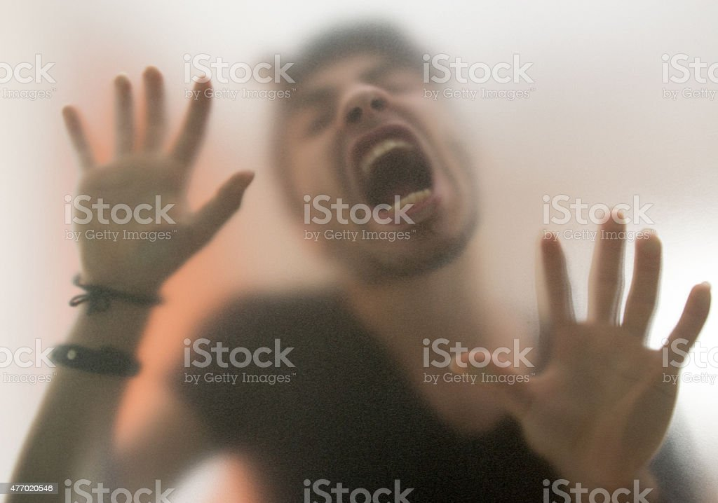 crazy man behind the glass wall stock photo