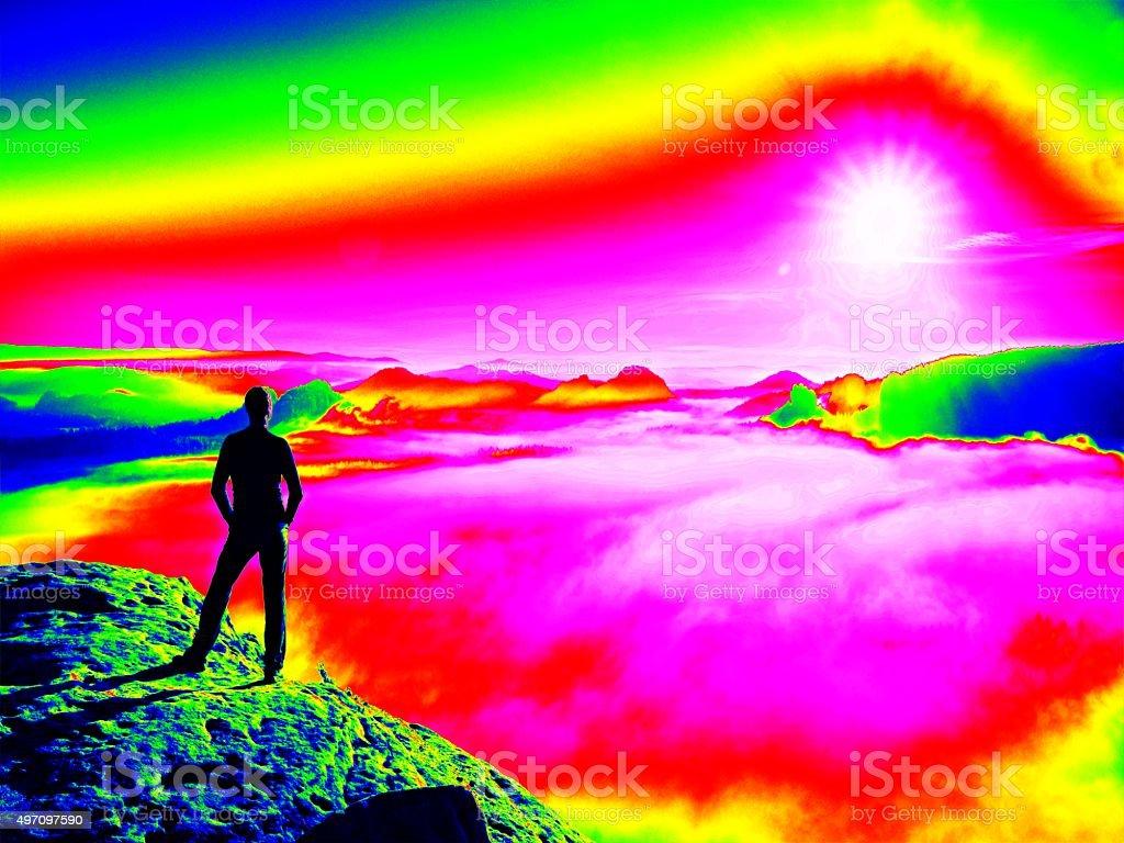 Crazy man. Fantastic infrared scan. Tourist on rocky peak. stock photo