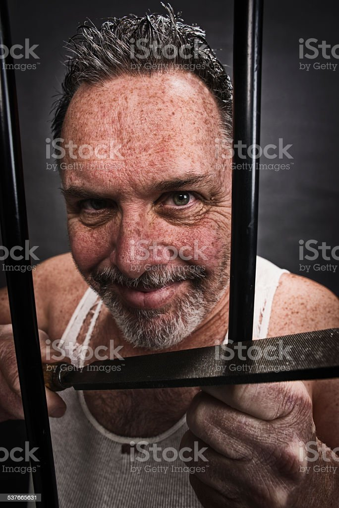 Crazy  man in jail with a file, trying to breakout stock photo