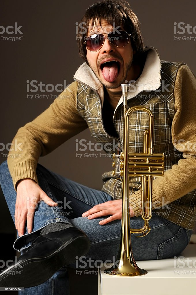 Crazy musician with golden trumpet is sticking out tongue stock photo