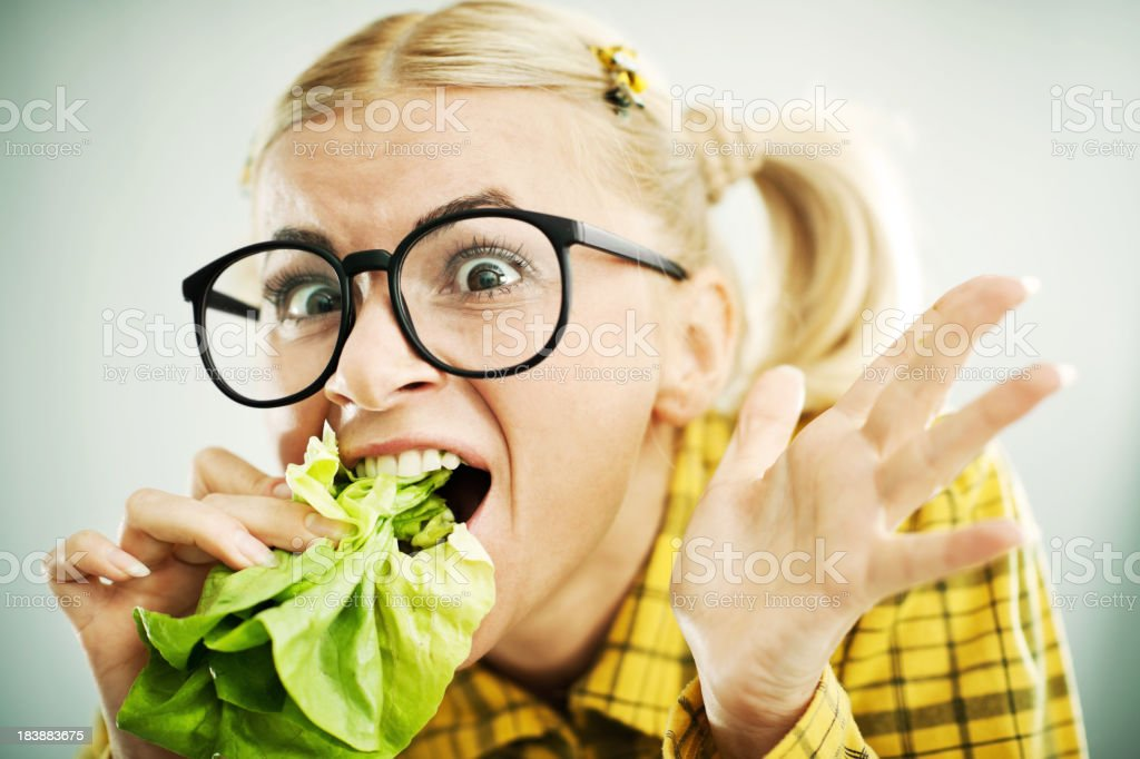 Crazy nerd woman with the cabbage leaf in her mouth. royalty-free stock photo