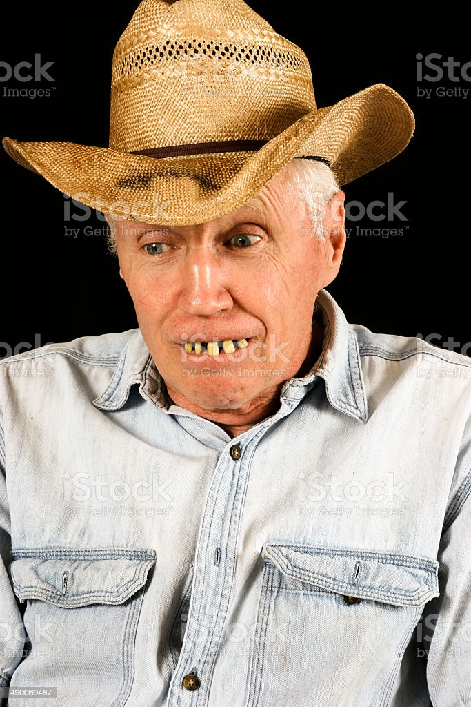 Ignorant, hillbilly old man cowboy with rotted teeth on black...