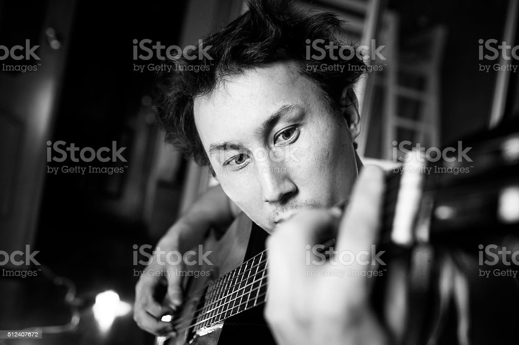 Crazy passionate guitarist playing guitar, black and white close-up stock photo