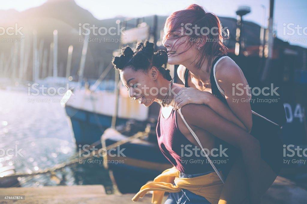 Crazy teen grunge girls piggybacking at the harbour stock photo