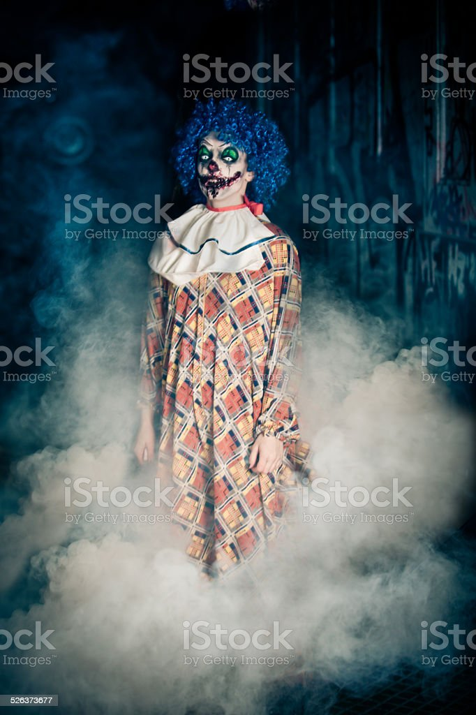 Crazy ugly grunge evil clown  making people shock and scared stock photo