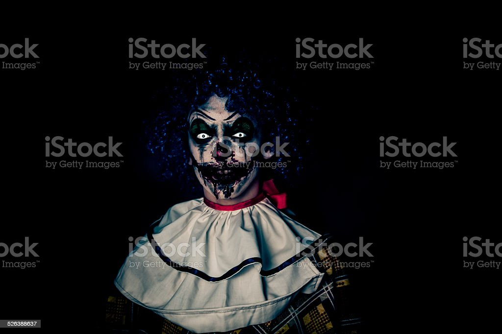 Crazy ugly grunge evil clown on Halloween making people scared stock photo