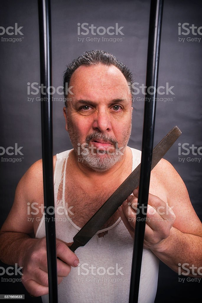 Crazy white man in jail with a large file stock photo