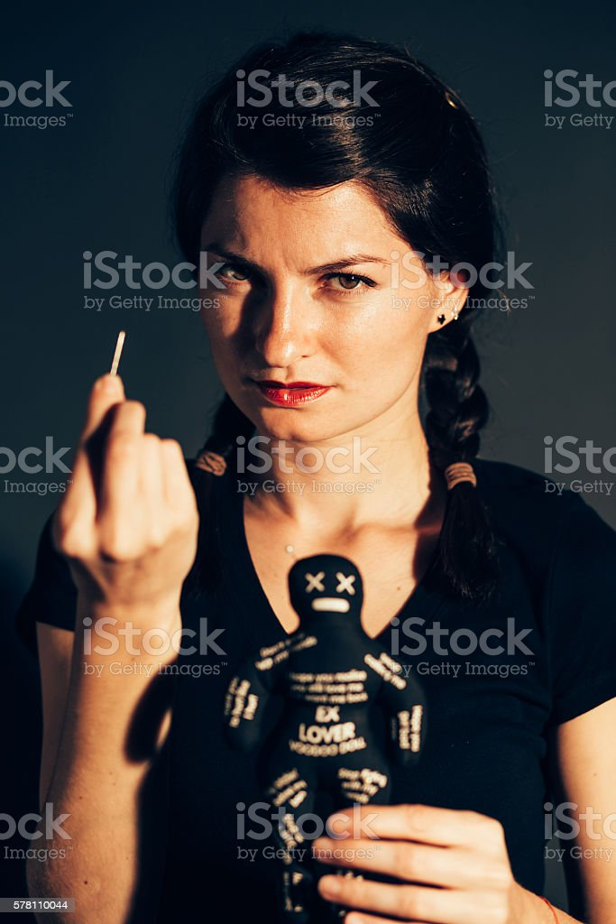 Crazy woman holding voodoo doll stock photo