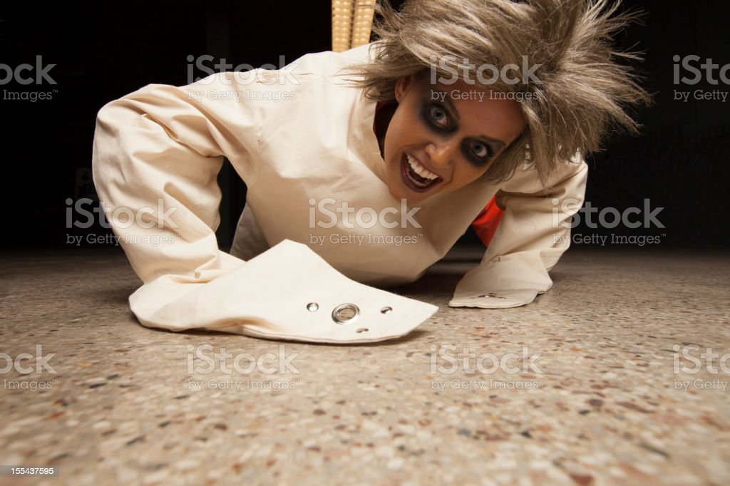 Crazy Woman wearing a straight jacket in an asylum crawling stock photo