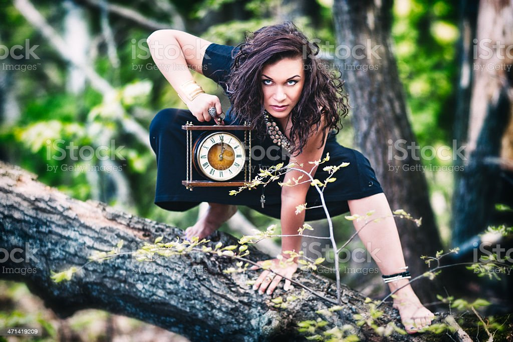 Crazy woman (witch) with old clock in the forest stock photo