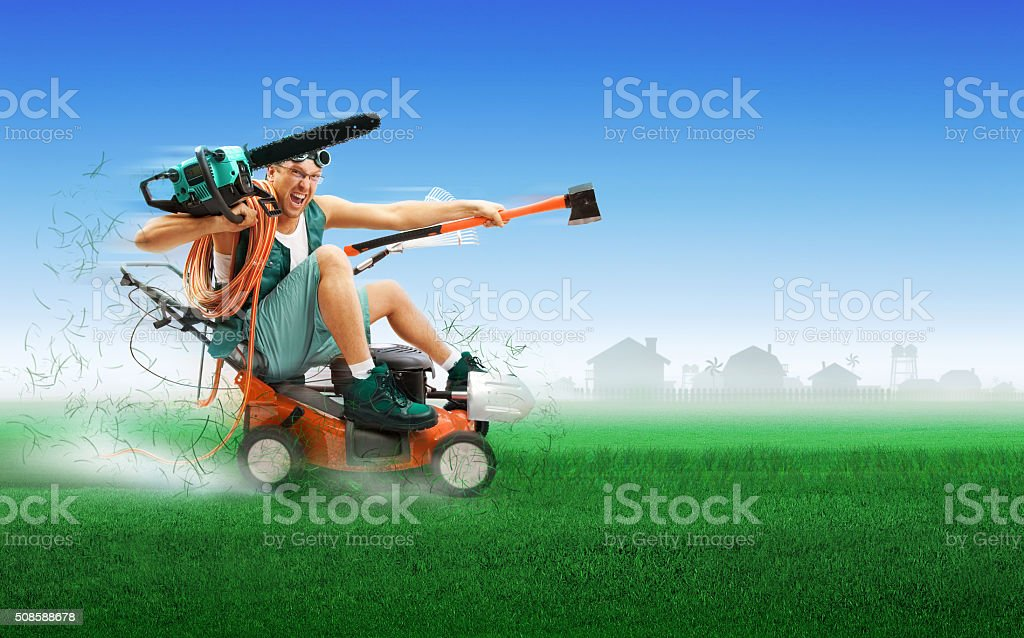 Crazy workman covered with instruments driving lawn mower stock photo