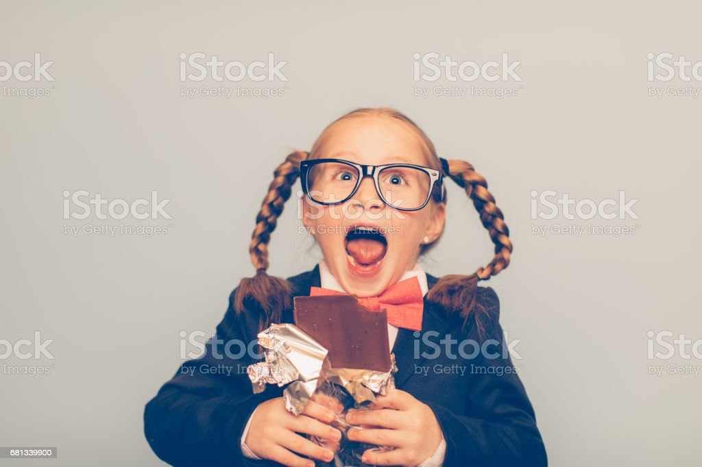 Crazy Young Female Nerd Eating a Chocolate Bar stock photo
