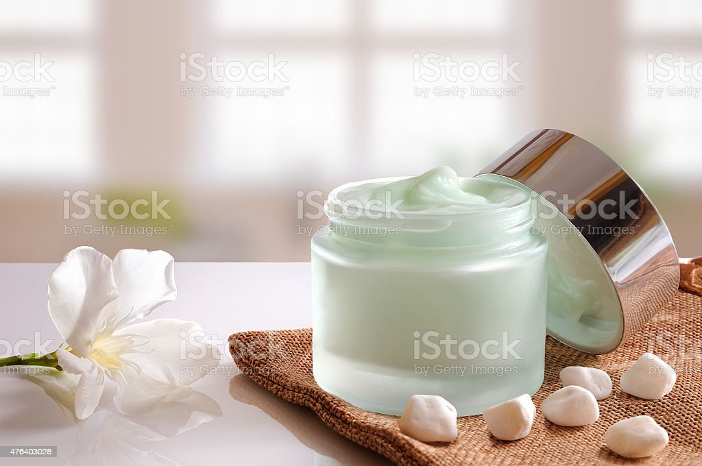 Cream jar open on burlap front view windows background stock photo