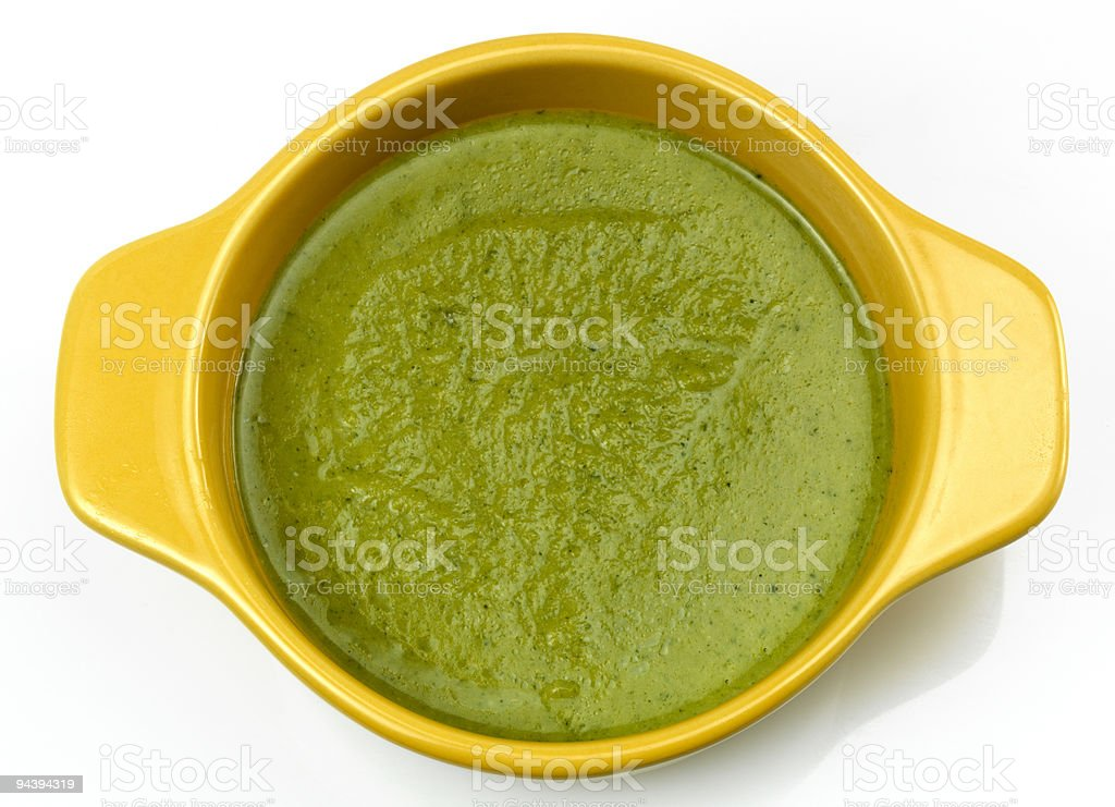 Cream of broccoli soup in yellow handled bowl. stock photo