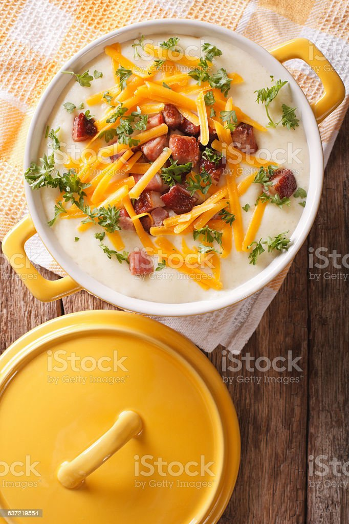 cream potato soup with bacon and cheddar cheese close-up. Vertical stock photo