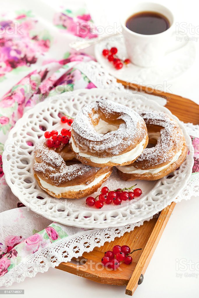 Cream puff rings decorated with fresh red currant stock photo